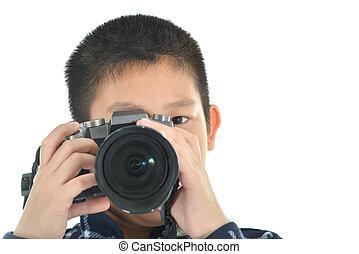 Asian boy holding camera on white background.