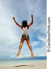 Asian boy jumping backwards on tropical beach