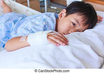 Asian boy lying on sickbed, saline intravenous (IV) on hand.