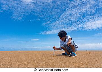 Asian boy play sand on the beach.
