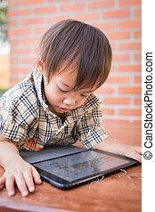 Asian boy play tablet fun