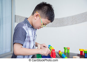 Asian boy playing blocks on table