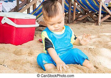 Asian boy playing sand on the beach