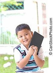 Asian boy playing Tablet fun