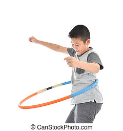 Asian boy playing with the hulahoop on a white background