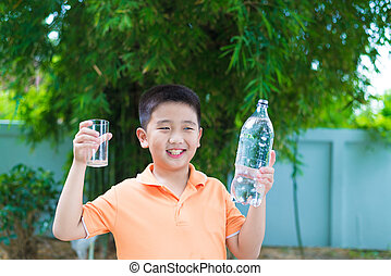 Asian boy pouring water into glass from bottle,