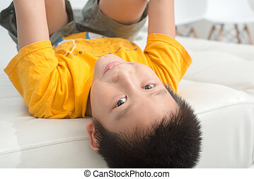 Asian boy resting comfortably on his bed