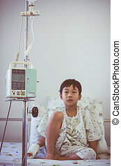 Asian boy sitting on sickbed with infusion pump intravenous IV drip. Retro style.