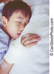 Asian boy sleeping on sickbed, saline intravenous (IV) on hand.