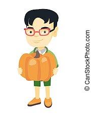 Asian boy standing with a big orange pumpkin.