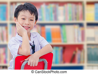 Asian boy student in uniform reading book in school library