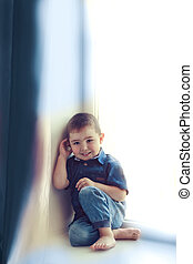 Asian boy three years sitting barefoot
