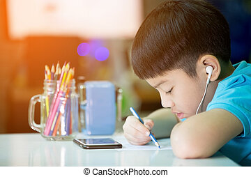 Asian boy using cellphone and painting on a white paper