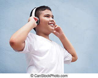 Asian boy wearing headphone over blue wall background.