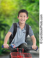 Asian boy with backpack riding a bike isolated on nature backgroun