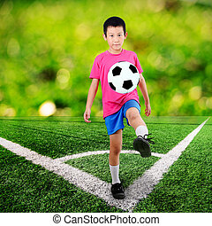 Asian boy with soccer ball at Corner of a soccer field and green