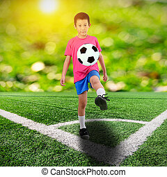 Asian boy with soccer ball on soccer field and orange bokeh and