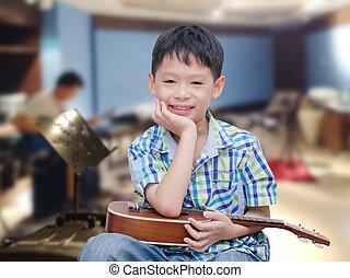 boy with ukulele at music school