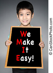 Asian boy  with WE MAKE IT EASY! message on black board