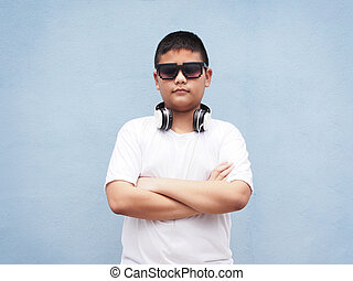 asian boy with white shirt wearing headphone over blue wall background.