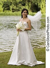 Asian Bride 17 - An asian woman stands near a lake in her...
