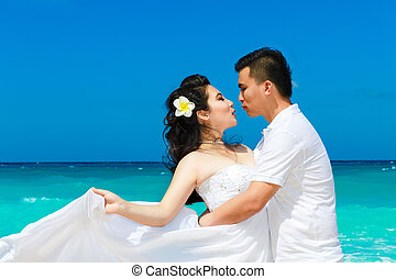 Asian bride and groom on a tropical beach. Wedding and...