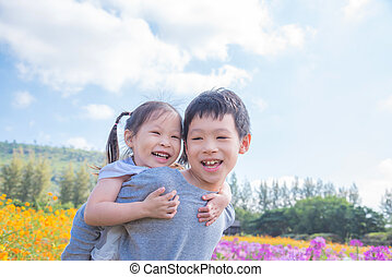 Asian brother holding his sister on his back and smiling together