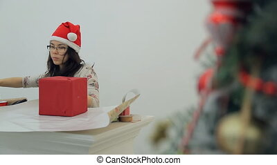 Asian brunette woman packing new year presents, decoration inside