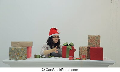 Asian brunette woman works with packing new year presents...