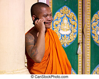 Asian buddhist monk talking with mobile phone in temple -...