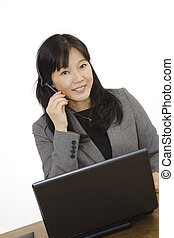 Beautiful Asain Businesswoman working on a laptop computer and talking on a telephone headset. She is photographed on a white background