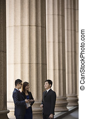 Asian business colleagues outside a Colonial building. -...