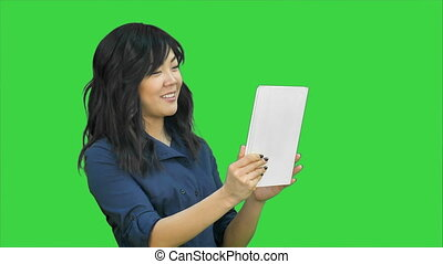 Asian business lady chatting using a tablet on a Green...