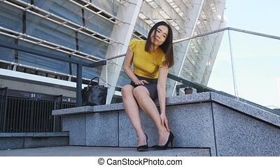 Asian business lady taking off heels of tired feet