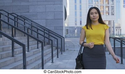 Asian business lady walking to job in the morning -...