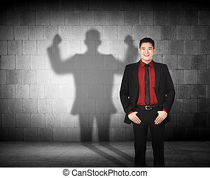 Asian business man casting a strong man shadow