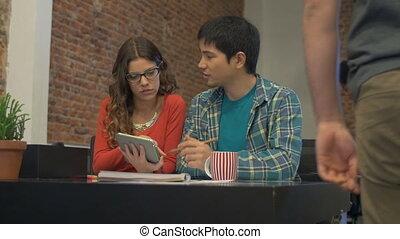 Asian Business man caucasian woman using tablet computer working office desk