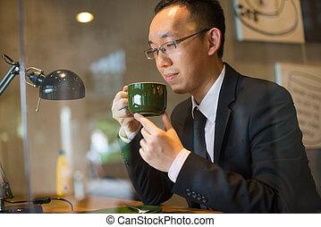 asian business man having coffee in cafe, hong kong