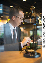 asian business man having coffee while surfing on tablet at cafe
