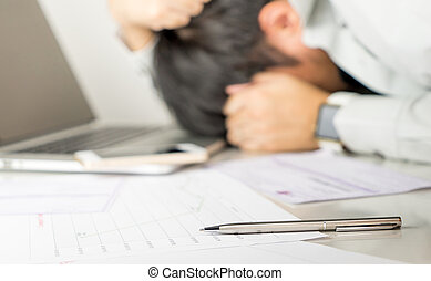 Asian Business man is stressed out on office table