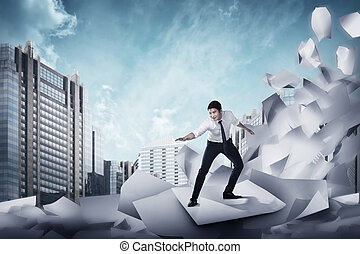 Asian business man surfing on the wave of papers