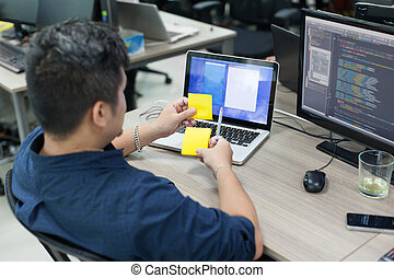 Asian business man yellow sticky note, rear back view thinking idea computer developer working desk laptop