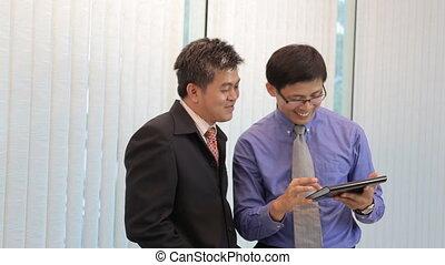 Asian business men using tablet