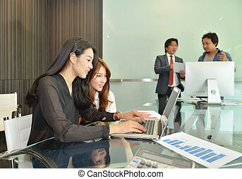 Asian business people discussing with each other