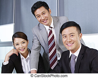 a team of asian business people looking at camera and smiling.