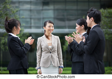 Asian business team congratulate a colleague. - Asian...