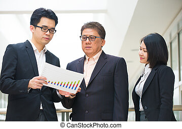 asian business team reporting to senior ceo with office ...