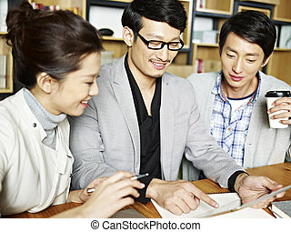 asian business team working together in office - a team of...