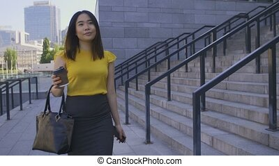 Asian business woman drinking coffee on the go - Beautiful...
