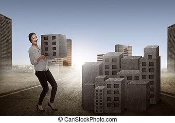 Asian business woman lifting block of city